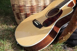 Beige brown wooden 6-strings classic acoustic guitar close up on wicker basket and green grass background at Sunny summer day - author bard songs symbol, tourist camp music art on outdoor recreation