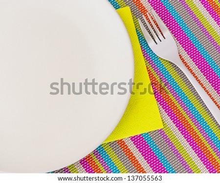 Beige ceramic plate, napkin and fork for food presentation