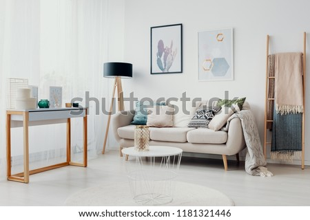 Beige couch between ladder and wooden lamp in white flat interior with posters and table. Real photo #1181321446