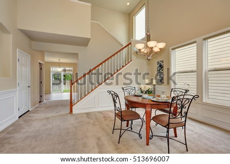 Photo of Beige dining room interior with high ceiling and staircase. Elegant table setting and wrought iron chairs. Northwest, USA