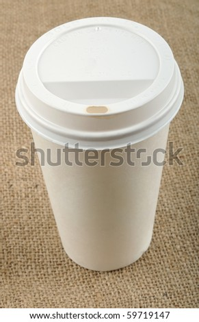 Beige disposable coffee cup on canvas.