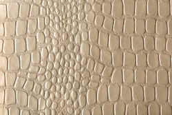 Beige, gold, glamorous croc-embossed artificial leather. For background and design.