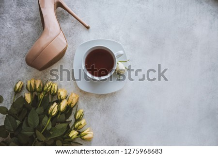 Beige high hills, bouquet of fresh flowers/roses and cup of tea on the white concrete background. Happy morning accessories. Fashion flat lay. Still life.  #1275968683