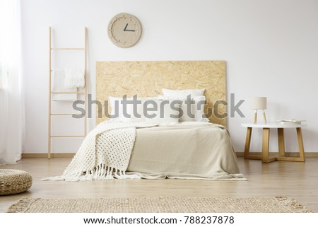 Beige, knit blanket on white bed with wooden bedhead next to a small table with lamp in minimalistic bedroom #788237878