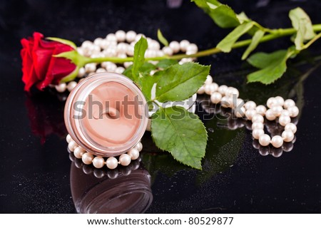 Beige liquid in the round glasses box with pearls,flowers and dropes water.