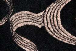 Beige loops on a black background. Textile background with abstraction. Beige striped waves on a fluffy background.