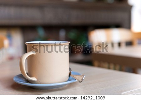 beige metal mug with a spoon on a saucer on a table in a cafe, coffee in a cafe #1429211009