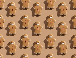 Beige pandemic art background. Seamless pattern. Christmas quarantine. Social distancing. Covid-19 winter holidays. Brown gingerbread man crowd in protective face masks isolated on light.
