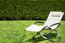 Beige rocking lounger on a green grass. Lounger outdoor, space for text