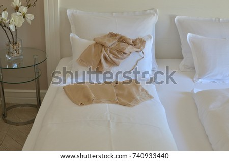 Beige silk babydoll on a bed with pillows and bedding