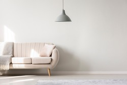 Beige sofa against white, empty wall with copy space in simple living room interior with lamp