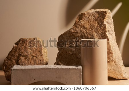Beige stone and a piece of grey podium tile on a beige background, natural background with shadow of tropical plant for your product Foto stock ©