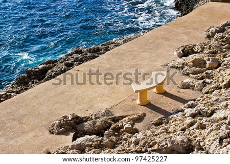 Beige Stone Bench At The Edge Of Bright Blue Rough Water