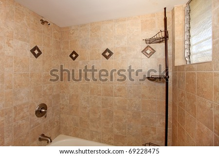 Beige stone tile shower with white tub