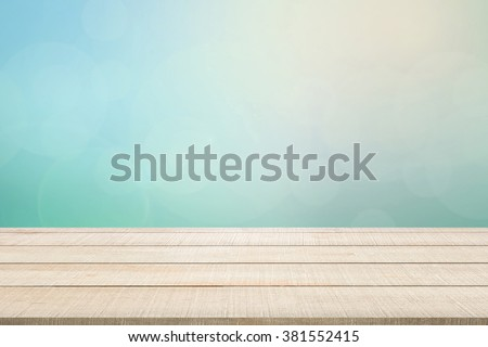 Beige wood table top panel on pastel blurred background in blue-turquoise tone with bright sunlight and flare, use for display or montage products for advertisement in natural summer concept