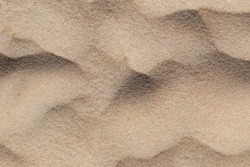 Beige yellow texture of sand on beach in heaps. Large and small grains of sand. Soft bumps.
