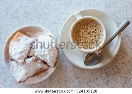 Beignets (French style donuts) topped with sugar and a cup of coffee in the background Stock fotó ©