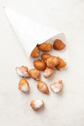 Beignets in a cornet paper bag on a stone surface