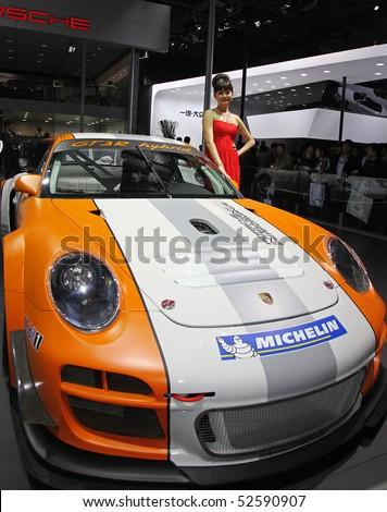 BEIJING - APRIL 29: A model stands beside a Porsche 911 GT3 R Hybrid at the 2010 Beijing International Automotive Exhibition (Auto China 2010) on April 29, 2010 in Beijing, China. - stock photo