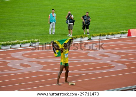 BEIJING - AUG 18: Usain Bolt celebrates holding the Jamaican flag after setting new world record  for men's 100 meter sprint at the 2008 Olympic. August 18, 2008 Beijing, China