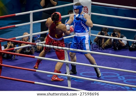 BEIJING - AUGUST  24: Roberto Cammarelle of Italy knocks out Zhilei ZHANG of China and goes on to win the gold in the Men's Super Heavyweight boxing final August 24, 2008 in Beijing, China. - stock photo