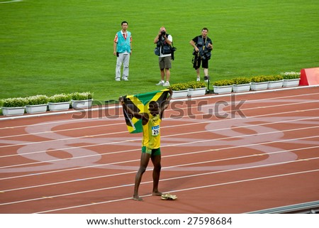 BEIJING - AUGUST 18: Usain Bolt celebrates holding the Jamaican flag after setting new world record  for men's 100 meter sprint at the 2008 Summer Olympic August 18, 2008 in Beijing, China.