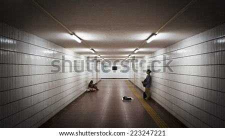 Beijing, China - August 3, 2014: One man is singing and anoter is begging in an underpass in China\'s capital Beijing.