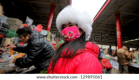BEIJING, CHINA - CIRCA JANUARY 2013: Unidentified woman with mask on antiques market, \