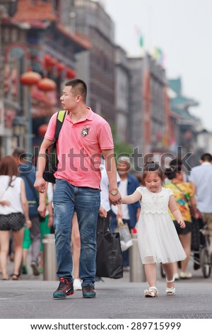 BEIJING, CHINA -JUNE 9, 2015. Chinese man with child. China\'s one-child policy, initiated late 1970s - early 1980s was to limit families have one child to reduce growth rate of China\'s enormous population.