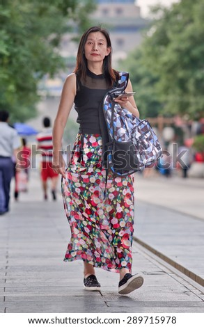 BEIJING, CHINA -JUNE 9, 2015. Fashionable, attractive woman walks in Qian Men Street. Over 27 years and unmarried females in China are labelled as leftover women, but many of them are happy being single.