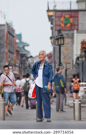 BEIJING, CHINA -JUNE 9, 2015. Handsome old man in city center. Elderly population (60 or older) in China is 128 million, one in every ten people, the world\'s largest. China has 400 million elderly by 2050.
