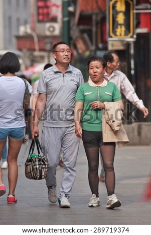 BEIJING, CHINA -JUNE 9, 2015. Middle-aged couple in city center. Recent study showed divorce rate among middle-aged Chinese couples has risen last two decades, while divorce rate among 20s couples has dropped