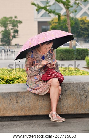 BEIJING, CHINA -JUNE 16, 2015. Middle-aged woman busy with her smartphone. China has currently 519.7 million smartphone users but that figure will rise to 574.2 million Chinese smartphone users by 2015.