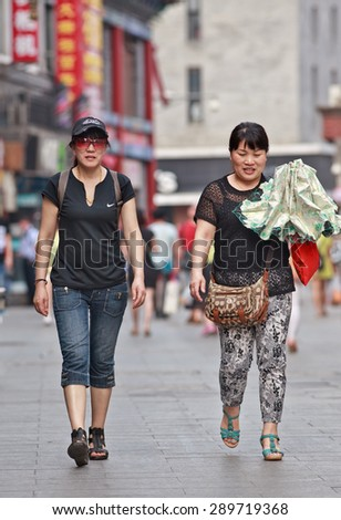 BEIJING, CHINA -JUNE 9, 2015. Middle aged woman in Beijing center. Lives of women in China have significantly changed after government made great efforts towards gender equality in a male-dominated society