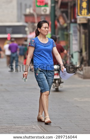 BEIJING, CHINA -JUNE 9, 2015. Middle-aged woman in shopping street. Lives of women in China have significantly changed after government made great efforts towards gender equality in a male-dominated society