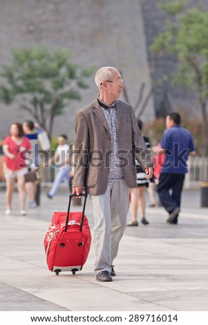 BEIJING, CHINA -JUNE 9, 2015. Old man with suitcase at Qian Men. Elderly population (60 or older) in China is 128 million, one in every ten people, the world\'s largest. China has 400 million elderly by 2050.