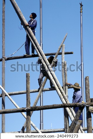 BEIJING, CHINA - JUNE 30, 1982: people work on a bamboo scaffold in Beijing, China. They wear the typical blue Mao uniform.