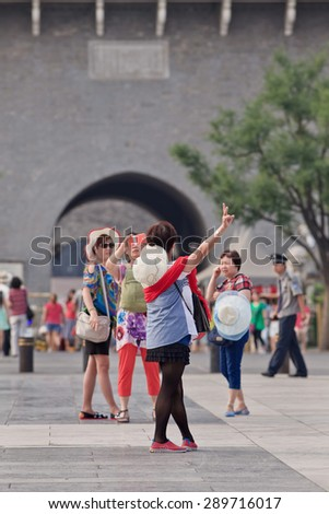 BEIJING, CHINA -JUNE 9, 2015. Woman takes photos with her smart phone at Qian Men. China has currently 519.7 million smartphone users. That figure will rise to 574.2 million Chinese smartphone users by 2015.