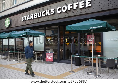 BEIJING, CHINA - NOV 10, 2013: A man is seen walking nearby a Starbucks coffee store. Starbucks is the largest coffeehouse company in the world, with 20,891 stores in 64 countries