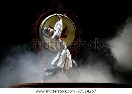 BEIJING, CHINA - NOVEMBER 16: A drummer performs the 'whipping drum' show on a giant drum on November 16, 2005 in Beijing, China. This dance is performed during major festivities in rural China.