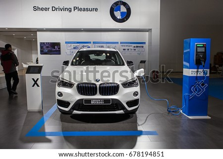 BEIJING, CHINA - OCTOBER 15, 2016: BMW X1 electric vehicle is connected to a electric charging station at the China International New Energy Automobile Exhibition at China National Convention Center #678194851