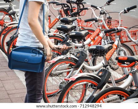Beijing, China - September 2017: Young woman making use of the Mobike bicycle sharing platform by using her smartphone to scan the QR code and unlock the bike #712948294