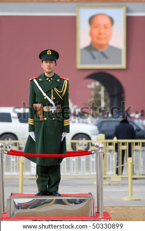BEIJING - FEB 19: a soldier stands guard in front of a portrait of Mao during spring festival on February 19, 2010 in Beijing, China. Crowds of people come to the capital to worship Mao - stock photo