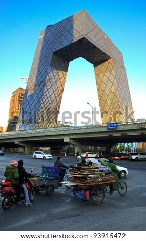 BEIJING-JANUARY 1: Workers and locals cycle around China Central Television (CCTV) Headquarters, a 234 m skyscraper, at dusk on Jan 1, 2011 in Beijing, China. CCTV is the National TV station of China.