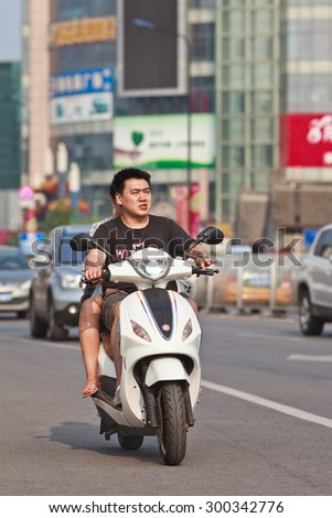 BEIJING-JULY 24, 2015. Couple on electric scooter. In a decade, e-bikes in China climbed from near zero to 150 million (2015), largest adoption of alternative fuel vehicle in history of motorization.
