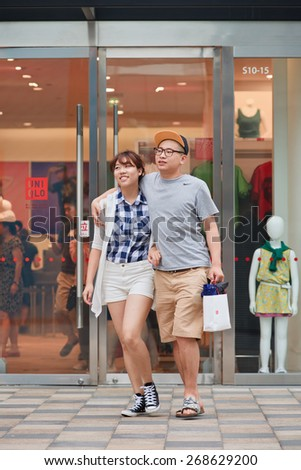 BEIJING-JULY 25, 2014. Happy young couple walks out UNIQLO outlet. UNIQLO opened its first store in China in Shanghai September 2002 and steadily expanded its network to 306 stores by August 2014.