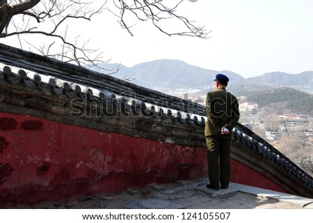 BEIJING - MAR 14:Chines man looks at the view from the top of Longevity Hill at the Summer Palace in Beijing,China on March 14 2007. The Summer Palace covers an expanse of 2.9 square kilometers.