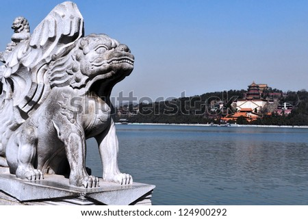 BEIJING - MAR 14:Marble Chinese lion sculpture against the Summer Palace on Kunming Lake  on March 14 2009. The Summer Palace is the best preserved imperial garden in the world.