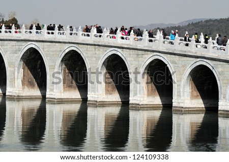 BEIJING - MAR 14:Visitors cross over the Seventeen-Arch Bridge at The Summer Palace in Beijing China on March 14 2009.The Summer Palace is the best preserved imperial garden in the world. - stock photo