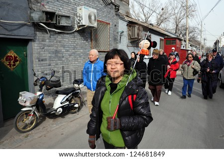 BEIJING - MARCH 11:A tour guide with tourists visiting a Hutong (old neighbourhood) on March 11 2009 in Beijing, China.There is around 4,000 Hutongs in Beijing some are hundreds of years old